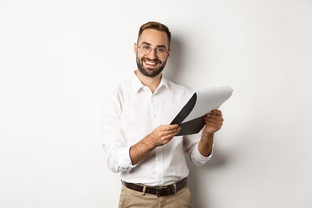 Empleador mirando satisfecho con cv, leyendo documento y sonriendo, de pie