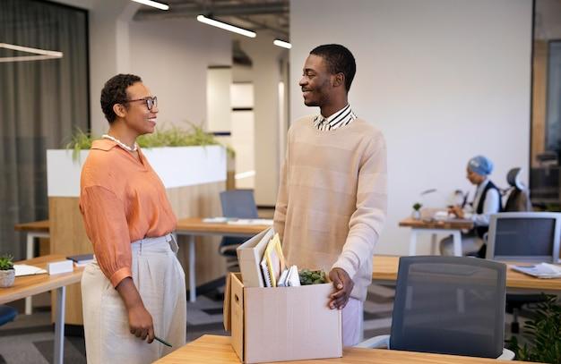 Empleador mostrando al hombre su escritorio en el nuevo trabajo mientras lleva una caja de pertenencias