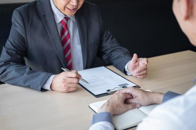 Empleador o reclutador que está leyendo un currículum durante una coloquio sobre su perfil de candidato