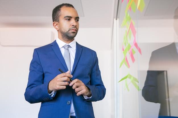 Empleador de oficina afroamericano sosteniendo la pluma y leyendo notas en la pared de vidrio. hombre de negocios confiado enfocado en traje pensando en la idea para el proyecto