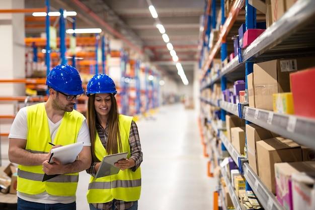 Empleados del almacén que trabajan juntos para contar productos y verificar el inventario en el centro de almacenamiento