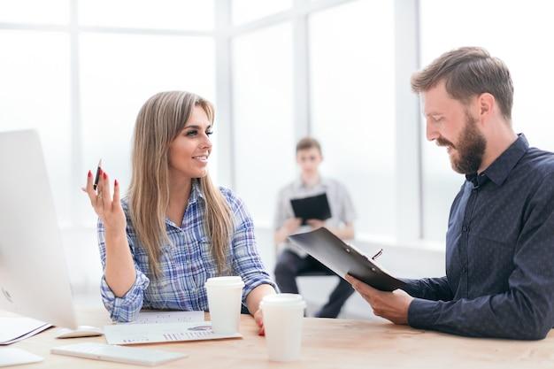 Empleados discutiendo documentos comerciales en la oficina.