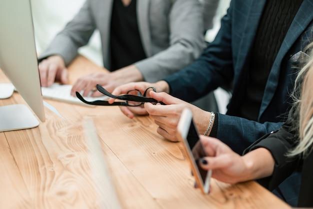 Empleados con dispositivos inteligentes sentados en el escritorio