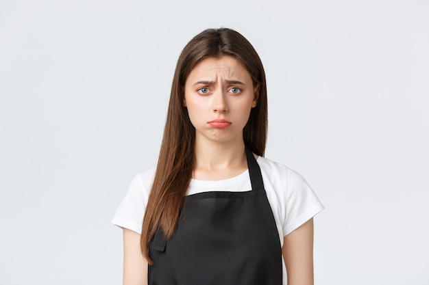 Empleados, empleo laboral, pequeñas empresas y concepto de cafetería. triste mujer barista decepcionada, cajera con delantal negro frunciendo el ceño inquieto, haciendo pucheros preocupado sobre fondo blanco.