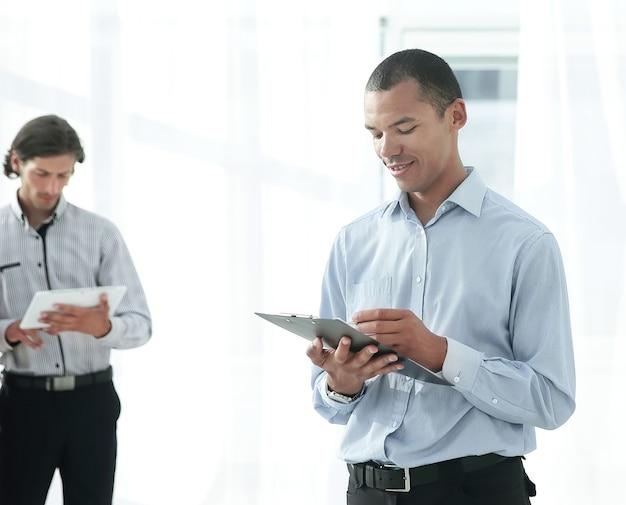 Empleados de la empresa antes de la reunión de pie en el vestíbulo de la oficina.