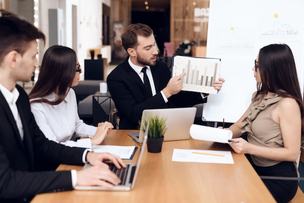 Los empleados de la empresa celebran una reunión en la mesa.