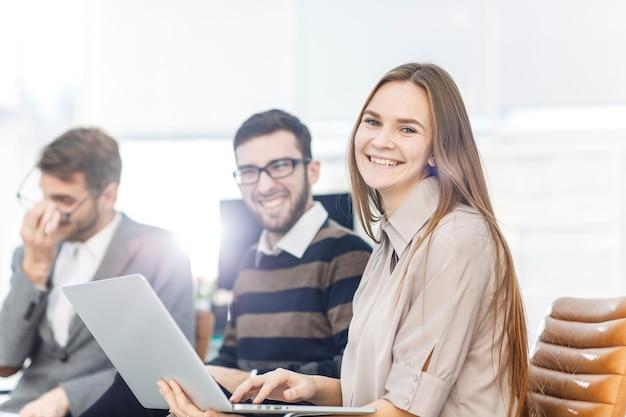 Los empleados de la empresa con una computadora portátil sentados en el vestíbulo de la oficina moderna.