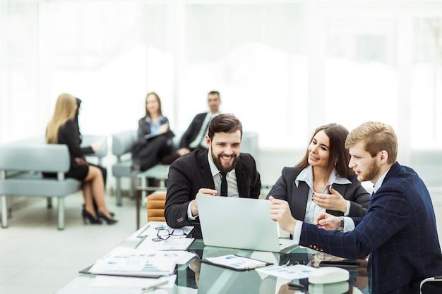 Los empleados de la empresa trabajan en una computadora portátil con información sobre el desarrollo de la empresa sentados detrás de un escritorio en la oficina.