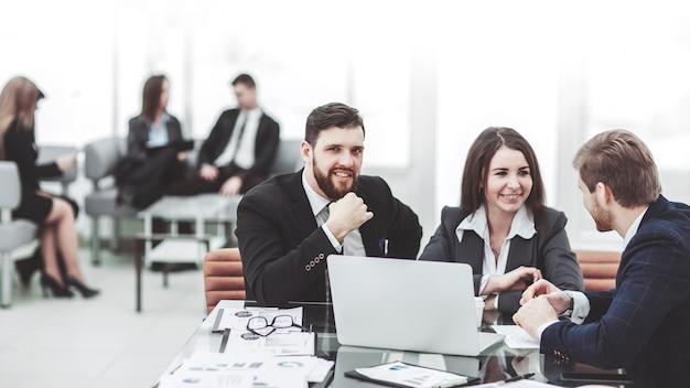 Los empleados de la empresa trabajan en una computadora portátil con información sobre el desarrollo de la empresa.