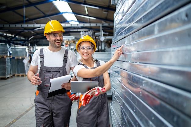 Empleados de la fábrica que controlan la calidad de los productos metálicos en la planta de producción