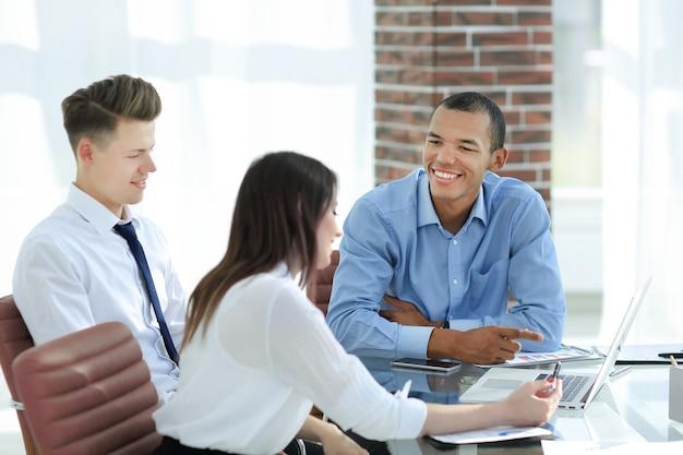 Empleados hablando con un cliente sentado en el escritorio