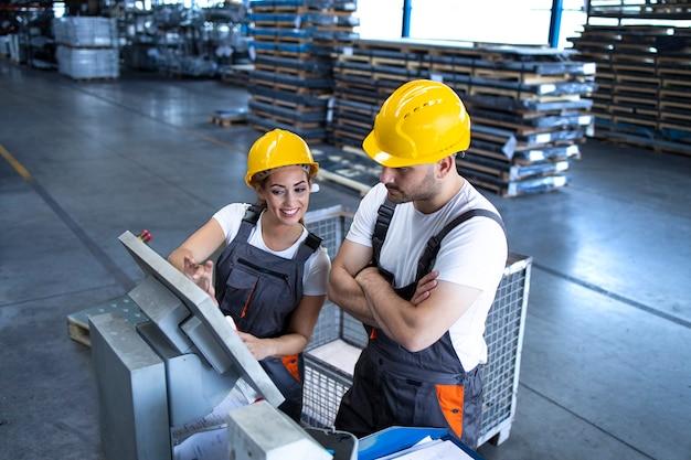 Empleados industriales con máquinas operativas de casco amarillo en la línea de producción utilizando un nuevo software informático