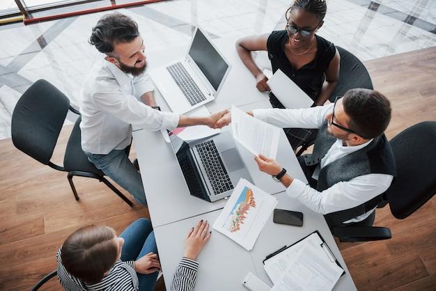 Empleados jóvenes sentados en la oficina en la mesa y usando una computadora portátil, un concepto de reunión de lluvia de ideas de trabajo en equipo.