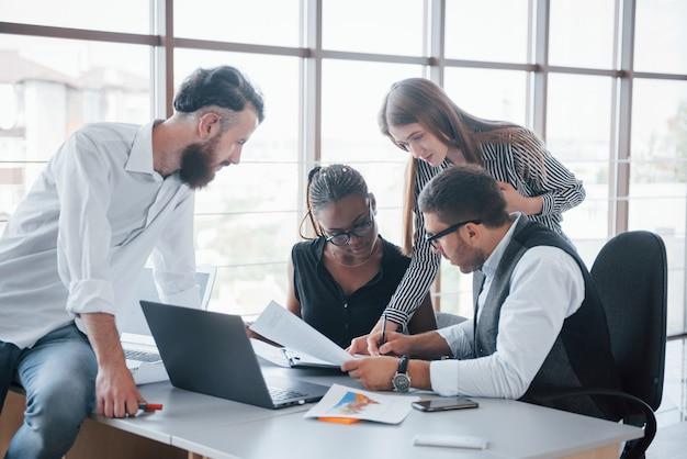 Empleados jóvenes sentados en la oficina en la mesa y usando una computadora portátil