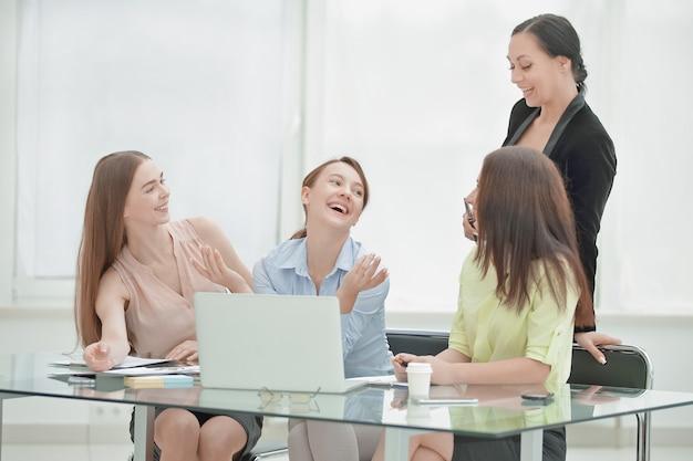 Empleados leyendo buenas noticias en línea en una computadora portátil sentada en un escritorio en la oficina.