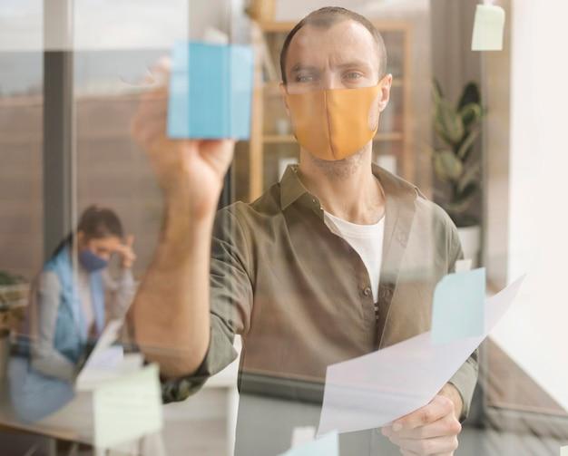 Empleados con máscaras faciales en la oficina.