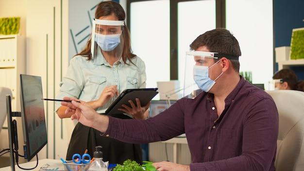 Empleados con máscaras de protección discutiendo mirando la computadora apuntando al escritorio analizando la lista de clientes en la nueva oficina normal durante la pandemia de covid-19. equipo multiétnico trabajando en empresa moderna.