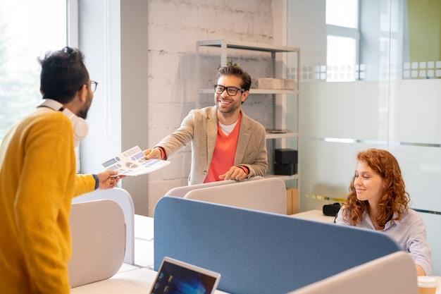 Empleados multiétnicos jóvenes amistosos alegres que trabajan en el informe financiero en la oficina: analista que pasa los documentos del informe al joven gerente