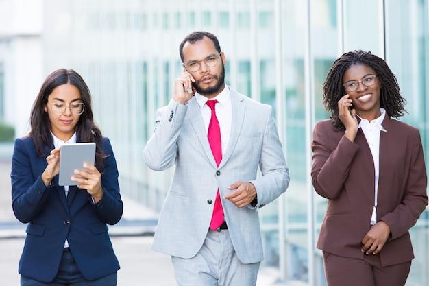 Empleados de oficina alegres caminando con dispositivos digitales