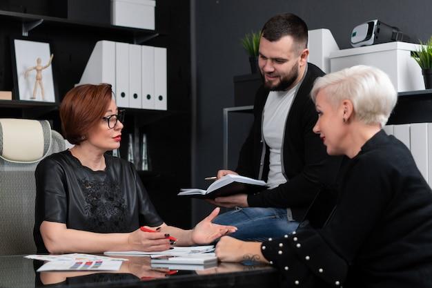 Empleados de oficina discuten su proyecto con una taza de té