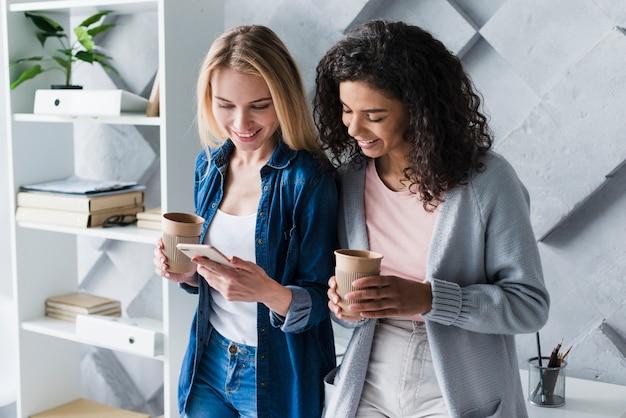Empleados de oficina étnicos femeninos en el descanso para tomar café con teléfono inteligente