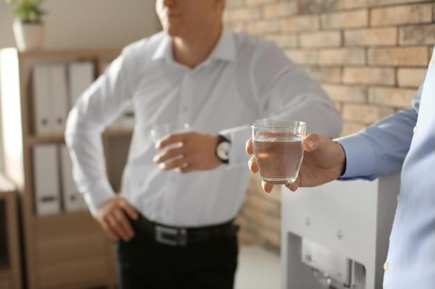 Empleados de oficina que tienen descanso cerca del enfriador de agua