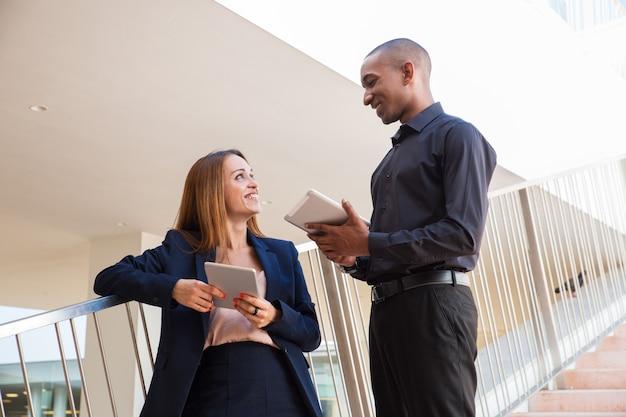 Empleados positivos charlando en la escalera