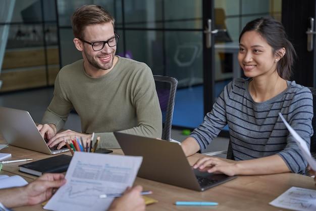 Empleados que trabajan en computadoras portátiles en reuniones con socios