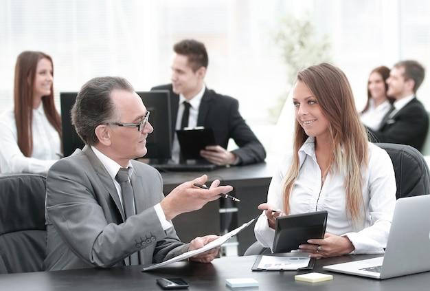 Empleados que usan tableta digital para trabajar con datos financieros