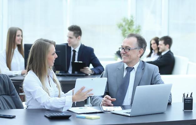 Empleados que utilizan tableta digital para trabajar con datos financieros, personas y tecnología.