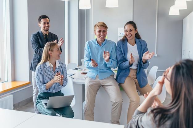 Los empleados se regocijan por su colega, aplauden y felicitan.