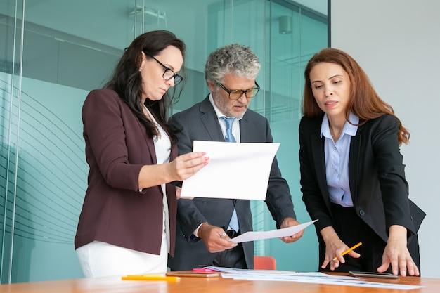 Empleados seguros discutiendo el proyecto juntos