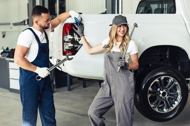 Empleados de servicio de automóviles posando con herramientas