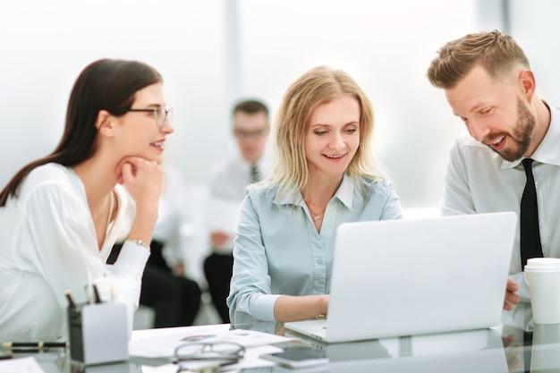 Empleados sonrientes sentados en el escritorio de oficina