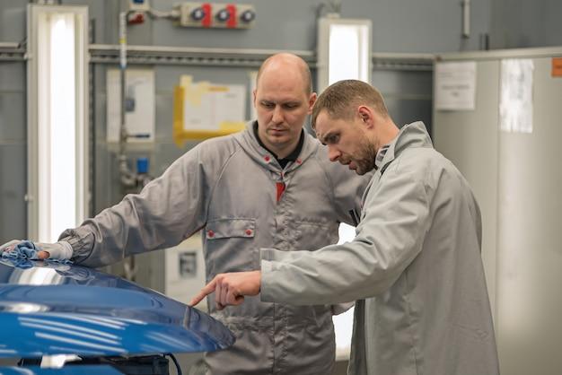 Los empleados del taller de pintura de carrocerías comprueban la calidad
