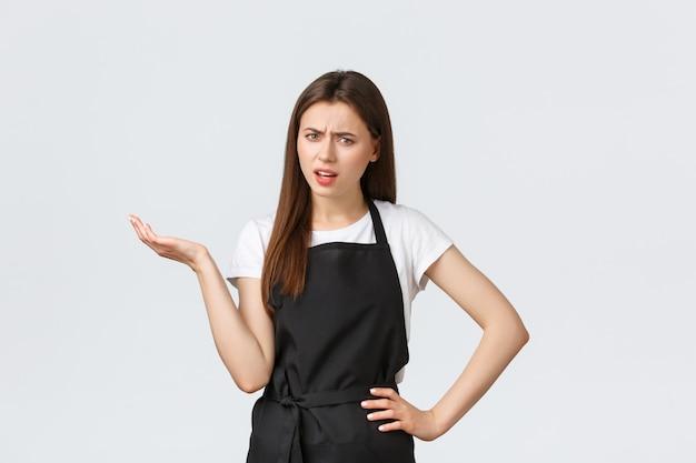 Empleados de la tienda de comestibles, pequeñas empresas y concepto de cafeterías. molesta escéptica barista con delantal negro diciendo qué. la vendedora levanta la mano consternada, molesta