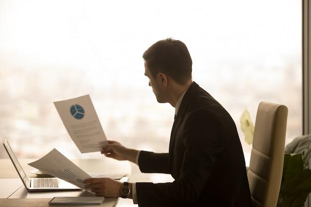 Emprendedor analizando documentos de estadísticas de negocios.