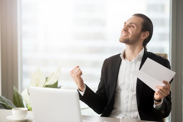 Emprendedor emocionado con logros en el trabajo.