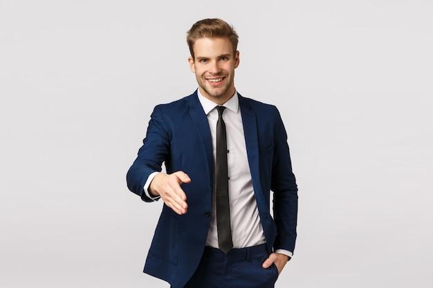 Emprendedor, empresarial y concepto corporativo. atractivo joven empresario rubio confiado y sonriente, extienda el brazo para un apretón de manos, diga que es un placer conocerte, saluda a los socios para hablar sobre ingresos y ofertas