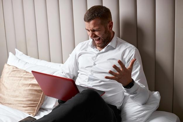 Emprendedor enojado y furioso con un portátil en la cama
