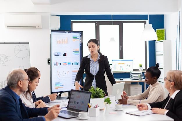 Emprendedor enojado en la sala de conferencias gritando a sus compañeros de trabajo en la sala de conferencias