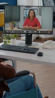 Emprendedor inmovilizado hablando con un compañero de trabajo durante la videoconferencia