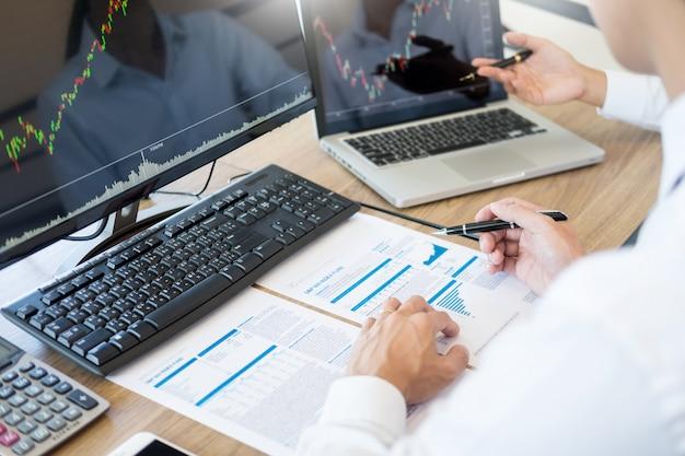 Emprendedor de inversiones del equipo que discute y analiza cuadros y gráficos comerciales en la computadora