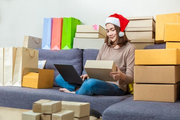 Emprendedor en línea femenino asiático joven del empresario, llevando el sombrero de la navidad, trabajando en su negocio en línea