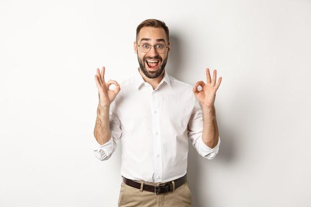 Emprendedor sorprendido que muestra el signo correcto y parece feliz, satisfecho con el producto, de pie blanco