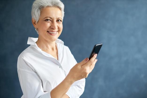 Emprendedora de mediana edad con cabello gris corto sosteniendo móvil, haciendo llamadas de negocios, escribiendo mensajes de texto.