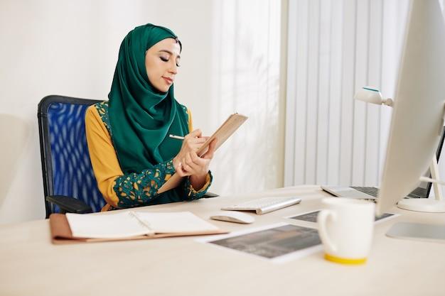 Emprendedora tomando notas en el planificador