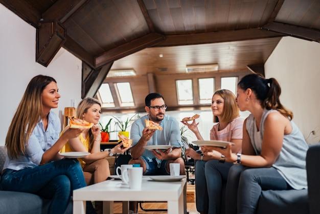 Emprendedores emprendedores comiendo pizza en espacio de coworking.
