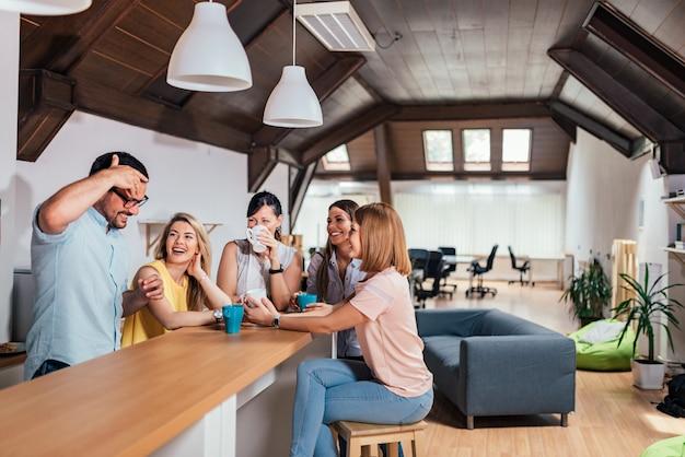 Emprendedores de empresas que toman un descanso en la oficina moderna de espacios abiertos.