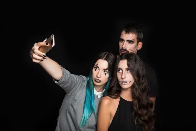 Empresa joven con espeluznante maquillaje tomando selfie